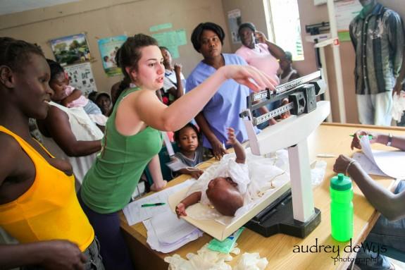Volunteer Julianna Piccirilli weighs an infant.